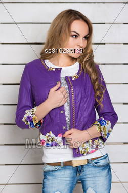 Portrait Of Curly Blond Woman In Purple Jacket Posing Near The White Wooden Wall Stock Photo