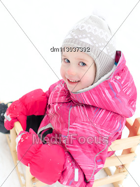 Portrait Of Cute Little Girl Sitting In Sled Stock Photo