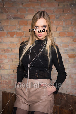 Portrait Of Fashionable Woman Posing Near Brick Wall Stock Photo