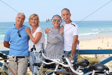 Portrait Of Four People At The Beach With Bikes Stock Photo