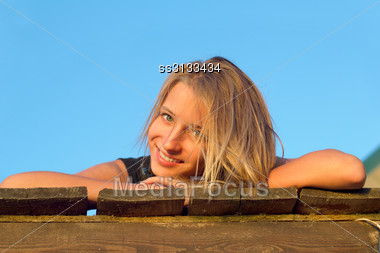 Portrait Of Girl Lying On A Wooden Flooring Stock Photo