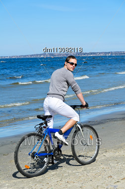 Portrait Of Handsome Male Riding A Bicycle By The Sea Stock Photo