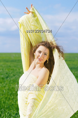 Portrait Of A Happy Young Woman Wrapped In Yellow Cloth Stock Photo