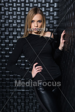 Portrait Of Inviting Young Woman Wearing Black Clothes Posing In Studio Stock Photo