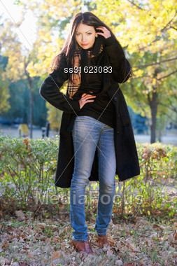 Portrait Of A Lovely Young Brunette In Autumn Park Stock Photo