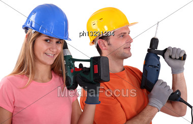 Portrait Of Male And Female Workers Holding Electric Drill Stock Photo