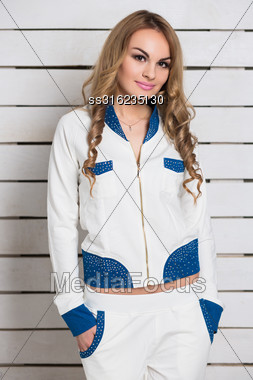 Portrait Of Nice Blonde In White And Blue Clothes Posing Near The Wall Stock Photo