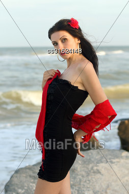 Portrait Of Nice Young Brunette In Black Dress On The Beach Stock Photo