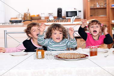 Portrait Of Children Eating At Table Stock Photo