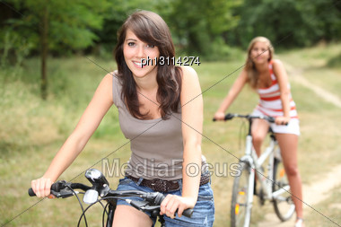 Portrait Of Two Girls On Bikes Stock Photo
