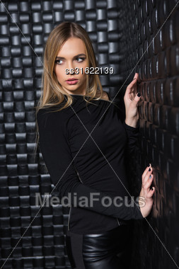 Portrait Of Pensive Young Woman Wearing Black Clothes Posing In Studio Stock Photo