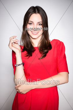 Portrait Of Playful Young Brunette Wearing Red Dress Stock Photo
