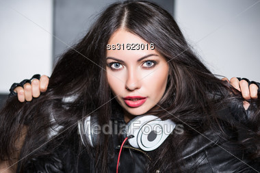 Portrait Of Playful Young Woman With Headphones Posing In The Studio Stock Photo