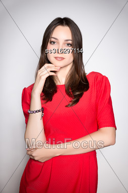 Portrait Of Playful Young Woman Wearing Red Dress Stock Photo