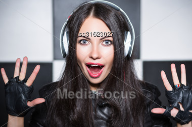 Portrait Of Playful Young Woman Yelling In Headphones Stock Photo