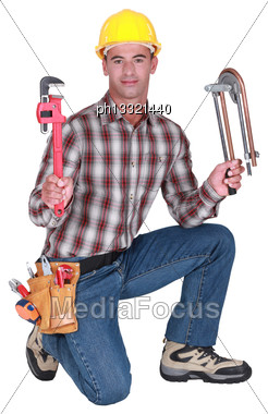 Portrait Of A Plumber With Tools In Both Hands Stock Photo