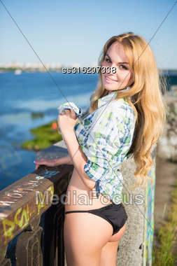 Portrait Of Pretty Blonde In Underwear And Shirt Posing Near The River Stock Photo