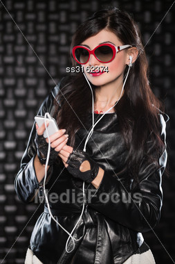 Portrait Of Pretty Brunette In Black Jacket Posing With Mobile Phone And Headsets Stock Photo