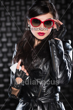Portrait Of Pretty Brunette In Black Jacket And Red Sunglasses Stock Photo