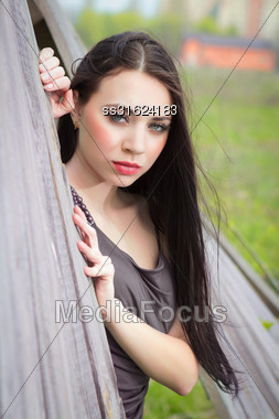 Portrait Of Pretty Brunette Posing Behind The Wooden Fence Stock Photo