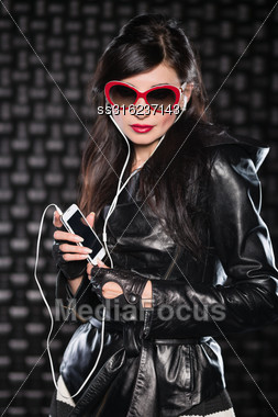 Portrait Of Pretty Brunette Posing With Mobile Phone And Headsets Stock Photo