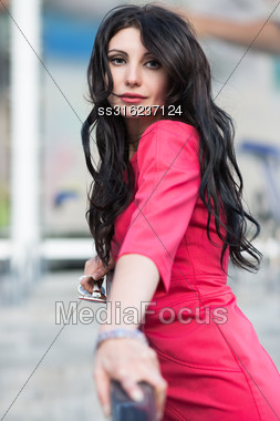Portrait Of Pretty Brunette In Red Dress Posing Outdoors Stock Photo