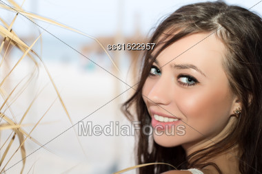 Portrait Of Pretty Cheerful Woman Posing On The Beach Stock Photo