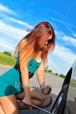 Portrait Of A Pretty Girl Changing Broken Tire On A Road Stock Photo
