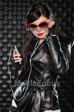Portrait Of Pretty Playful Brunette In Black Jacket Posing With Mobile Phone And Headsets Stock Photo