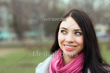 Portrait Of Pretty Smiling Brunette With Pink Scarf Posing Outside Stock Photo