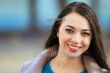Portrait Of Pretty Smiling Brunette Posing Outdoors Stock Photo