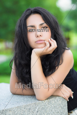 Portrait Of Pretty Thoughtful Brunette Posing Near Stone Fence Stock Photo