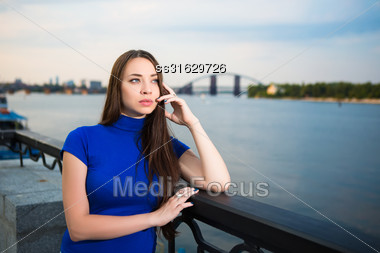 Portrait Of Pretty Thoughtful Brunette Posing Near The River Stock Photo