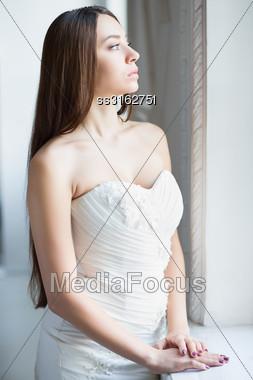 Portrait Of Pretty Thoughtful Brunette Posing In Wedding Dress Stock Photo
