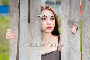 Portrait Of Pretty Thoughtful Woman Posing Behind The Wooden Fence Stock Photo