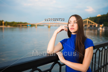 Portrait Of Pretty Thoughtful Young Brunette Posing Near The River Stock Photo