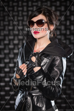 Portrait Of Pretty Woman Posing In Black Jacket With Hood And Sunglasses Stock Photo