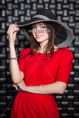 Portrait Of Pretty Woman Posing In Red Dress And Hat Stock Photo