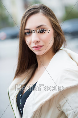 Portrait Of Pretty Woman In White Jacket Posing Outdoors Stock Photo