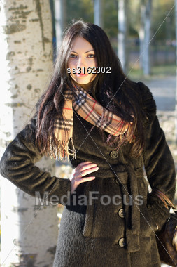 Portrait Of A Pretty Young Brunette In Autumn Park Stock Photo