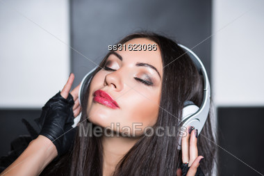 Portrait Of Pretty Young Brunette With Closed Eyes And Headphones Stock Photo