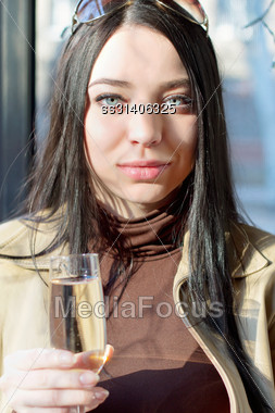 Portrait Of Pretty Young Brunette With A Glass Of Champagne. Isolated On White Stock Photo
