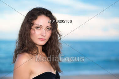 Portrait Of Pretty Young Brunette Posing On The Beach Stock Photo