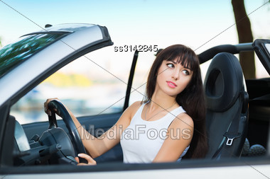 Portrait Of Pretty Young Brunette Posing In Cabriolet Stock Photo
