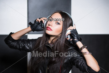 Portrait Of Pretty Young Brunette Posing In The Studio With Headphones Stock Photo