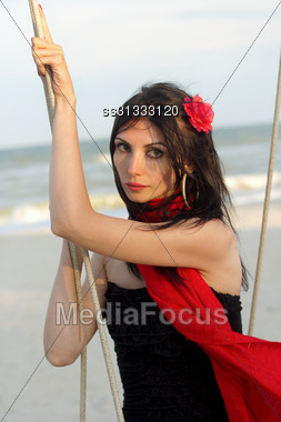 Portrait Of Pretty Young Woman Sitting On A Swing Stock Photo