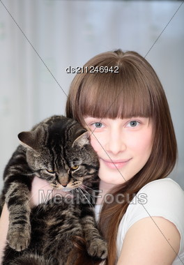 Portrait Of A Relaxed Young Woman Smiling Indoors With Cat Stock Photo