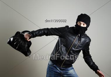 Portrait Of Running Male Burglar With A Handbag Stock Photo