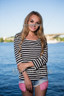 Portrait Of Sexy Blonde In Striped Blouse And Jeans Short Posing Near The River Stock Photo