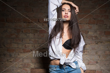 Portrait Of Sexy Brunette Posing In Black Bra And White Shirt Stock Photo